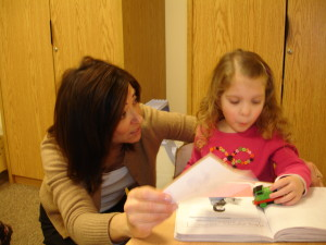 Speech Language Pathologist Madi Waldner helps child pratice speech sounds